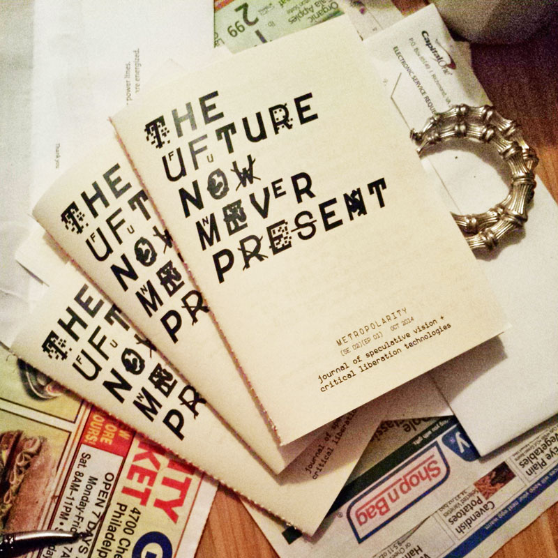 three copies of the future now zine fanned out over top grocery store circulars, misc mail, and bamboo hoop earrings