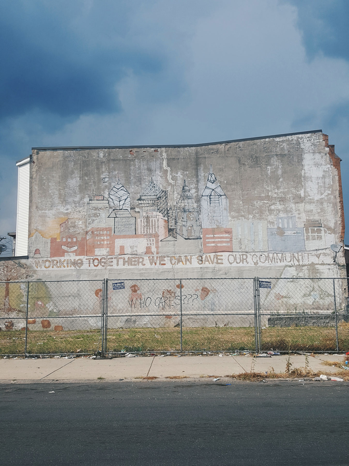 A photo of a faded mural depicting the pre-Comcast Center Philadelphia skyline, with the words Working Together We Can Save Our Community. The mural is behind a fenced in lot where a house once stood. Someone has spray painted WHO CARES??? underneath the original message.