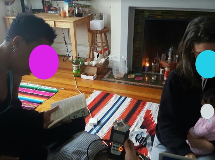 A sunlit room. Ras sits on the left reading her story while Eighteen's hand holds a field recorder, and our neighbor Althea holds a baby and performs the ambient audio accompaniment